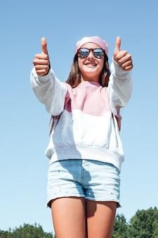 Donna ragazza con occhiali da sole e foulard rosa in testa, alzando i pollici. giornata internazionale del cancro al seno, con il cielo sullo sfondo.