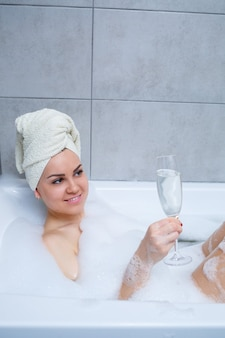 Ragazza donna con un asciugamano bianco sulla testa giace con un bicchiere di champagne in una vasca da bagno bianca. nelle sue mani un sacco di sapone per la pipì. schiuma idromassaggio completa. rilassati dopo una dura giornata. procedura di rilassamento termale