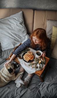 Una ragazza in calzini di lana fa colazione con waffle caldi a letto con il suo amico carlino.