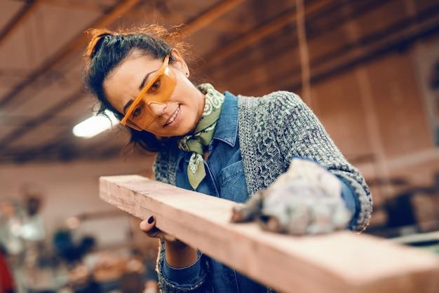 Ragazza che lavora con la plancia di legno che indossa l'equipaggiamento protettivo.