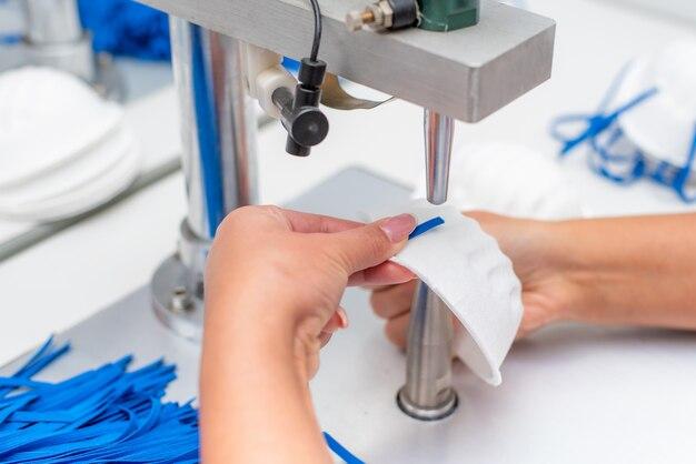 La ragazza lavora in una fabbrica per la produzione di maschere mediche con nanofibre e anelli di saldatura con ultrasuoni su una macchina.