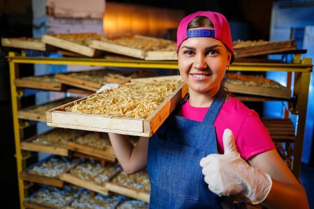 La ragazza lavora alla produzione di spaghetti. fare le tagliatelle. pastificio. fase di produzione della pasta. tagliatelle crude. operaio con una scatola di pasta.