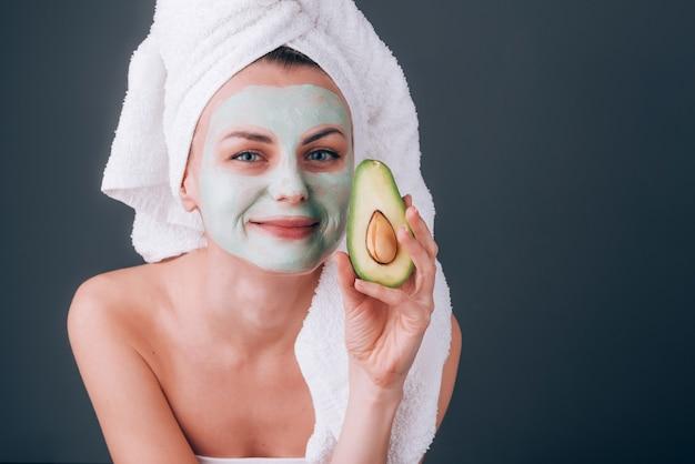 Ragazza avvolta in un asciugamano con una maschera cosmetica sul viso e avocado tra le mani