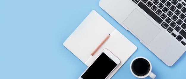 La ragazza scrive sul libro bianco aperto o sulla contabilità su una scrivania azzurra pulita minima con laptop e accessori, spazio copia, vista piana, vista dall'alto, mock up