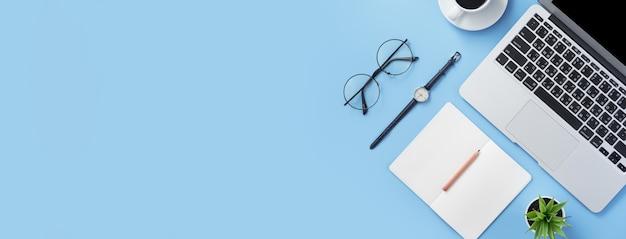La ragazza scrive sul libro bianco aperto o sulla contabilità su una scrivania azzurra pulita minima con laptop e accessori