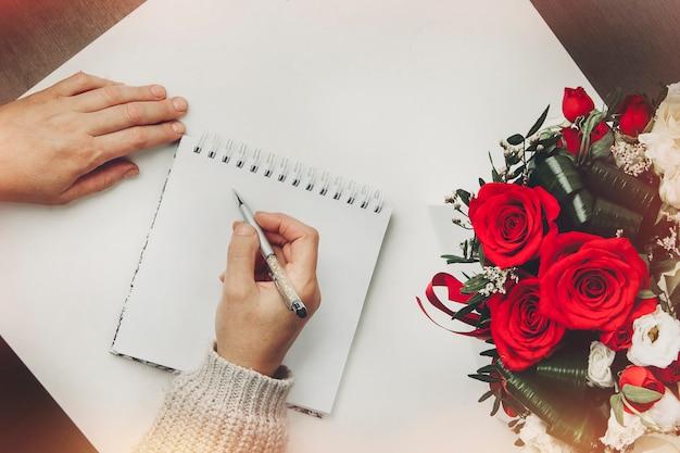 La ragazza scrive in un taccuino vista dall'alto