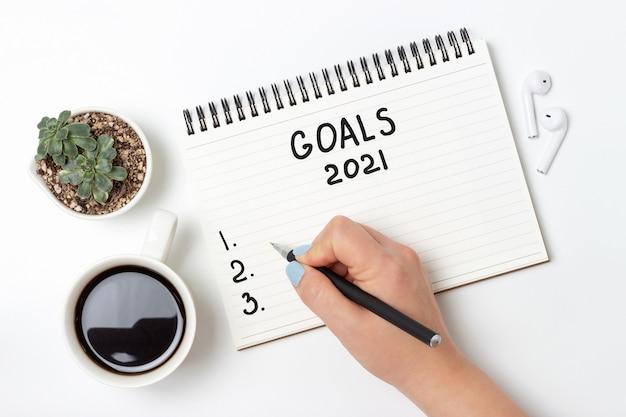 La ragazza scrive nel blocco note dell'obiettivo per il 2021