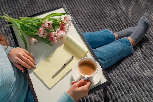Ragazza che scrive la lista dei desideri per i piani futuri. fiori, blocco note, una tazza di caffè