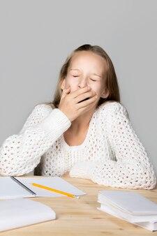 Ragazza di sbadiglio durante gli studi
