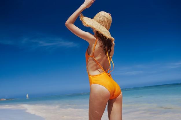 Ragazza in costume da bagno giallo e cappello su una spiaggia bianca come la neve