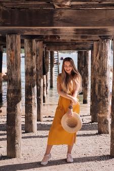 Ragazza in abito giallo e cappello in piedi sotto un molo in legno. guarda la fotocamera.