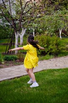 Una ragazza con un vestito giallo si gira su se stessa in una danza su una radura verde nella foresta, divertendosi durante un...