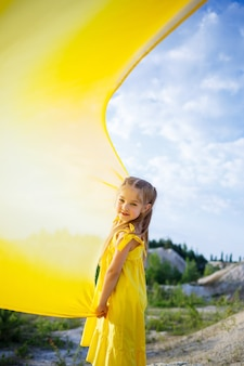 Ragazza in un vestito giallo con le ali in un panno giallo vicino al lago