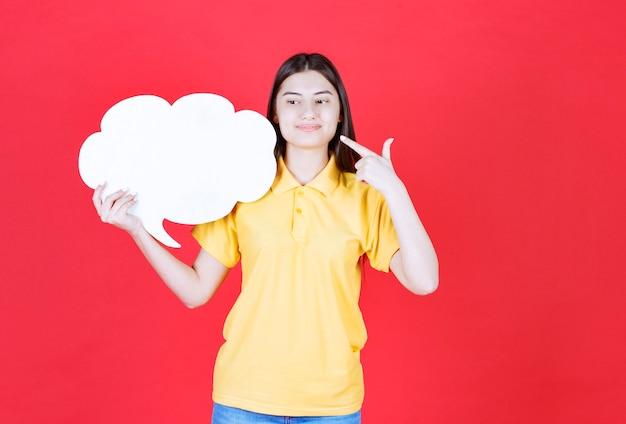 Ragazza in codice di abbigliamento giallo che tiene una scheda informativa a forma di nuvola.