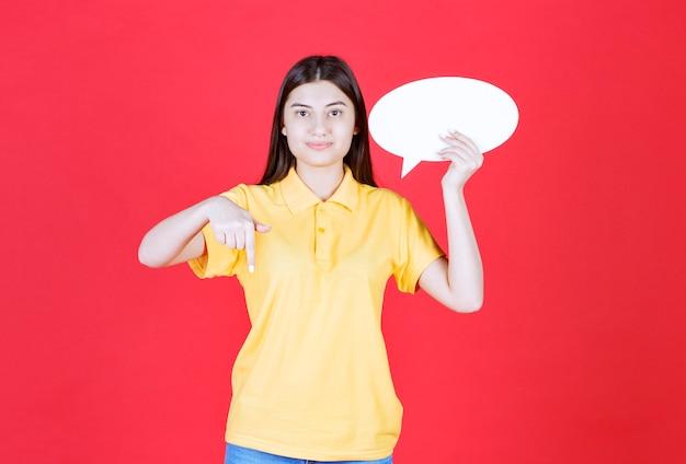 Ragazza in codice di abbigliamento giallo con in mano un pannello informativo ovale