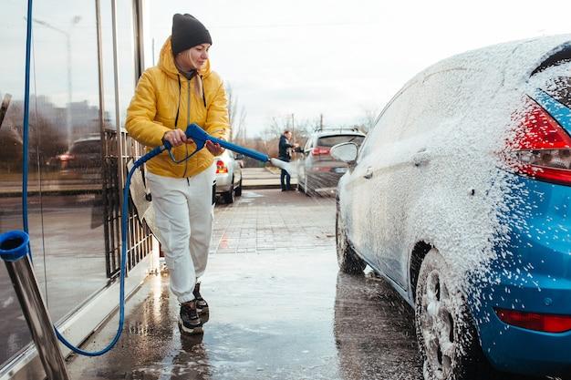 La ragazza in una giacca gialla applica la schiuma sull'auto