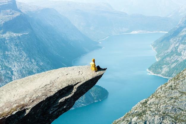 Una ragazza con una giacca gialla si siede sul trolltunga in norvegia