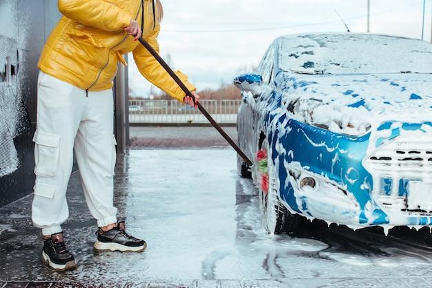 Una ragazza in giacca gialla con una spazzola lava una ruota in un autolavaggio self-service