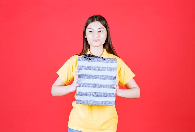 Ragazza in camicia gialla che tiene una borsa della spesa blu.