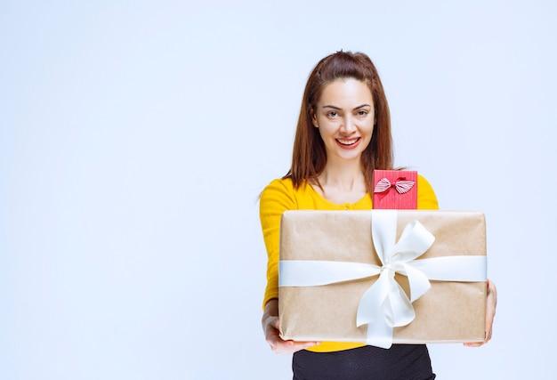 Ragazza in camicia gialla che tiene scatole regalo e dandole al cliente.