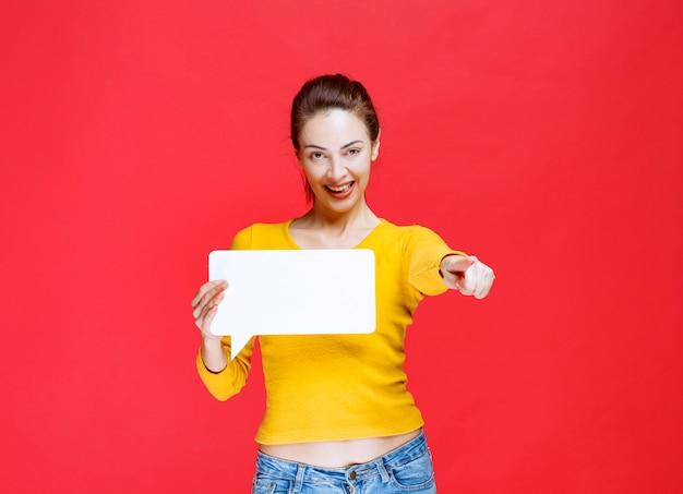 Ragazza in camicia gialla che tiene in mano una bacheca informativa rettangolare e indica la persona avanti