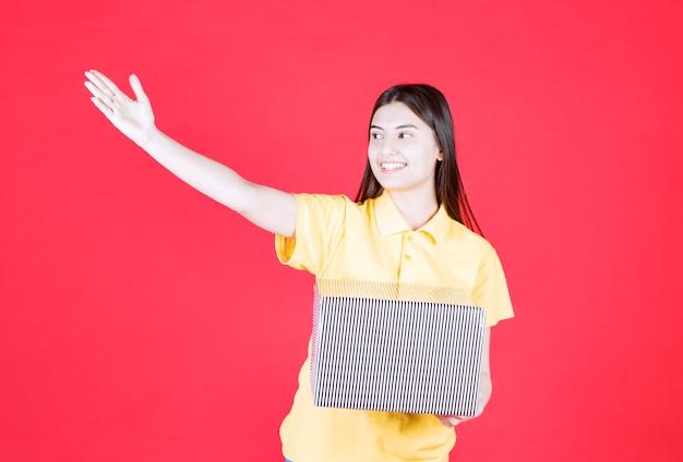 Ragazza in camicia gialla che tiene in mano una confezione regalo d'argento e invita qualcuno a incontrarsi.