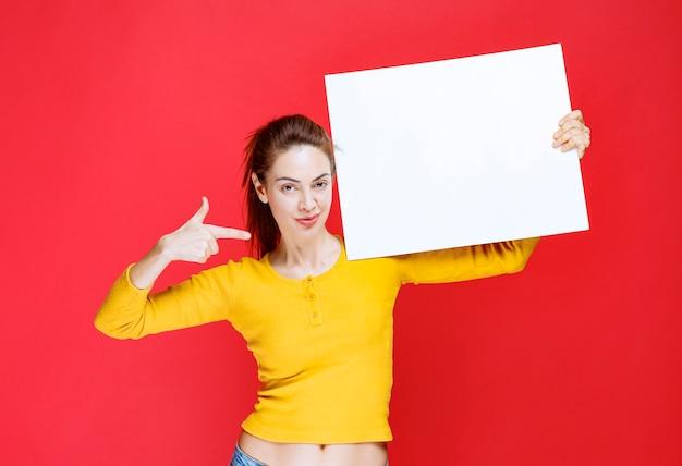 Ragazza in camicia gialla con in mano un pannello informativo quadrato
