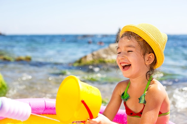 Ragazza in cappello di paglia giallo gioca con il vento, l'acqua e un distributore di acqua in una piscina gonfiabile sulla spiaggia. prodotti indelebili per proteggere la pelle dei bambini dal sole, dalle scottature. resort al mare.