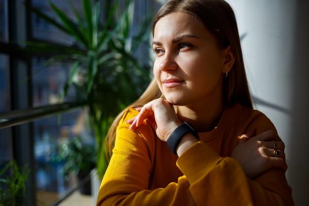 La ragazza con un maglione giallo si siede vicino a una grande finestra con un telefono rosso.