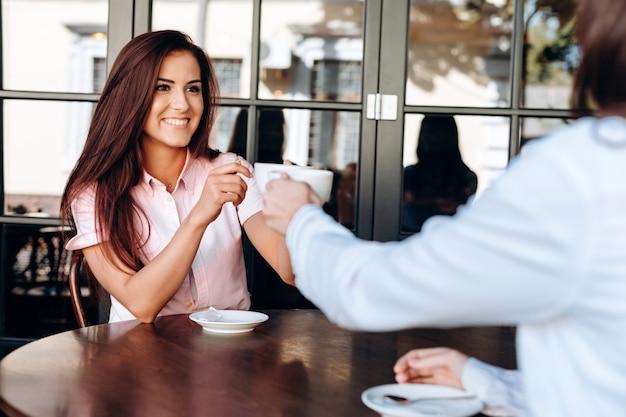 Una ragazza e un giovane carico tintinnano due tazze da caffè su un tavolo di legno in un caffè
