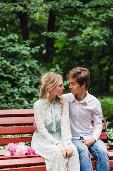 Ragazza e giovane uomo seduto su una panchina, primo appuntamento, comunicazione bacio, conoscenza