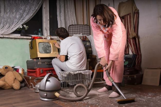 Fidanzata in abito rosa che pulisce una stanza abbandonata usando l'aspirapolvere mentre il fidanzato è impegnato a lavorare con vecchi oggetti inutilizzati sul retro.