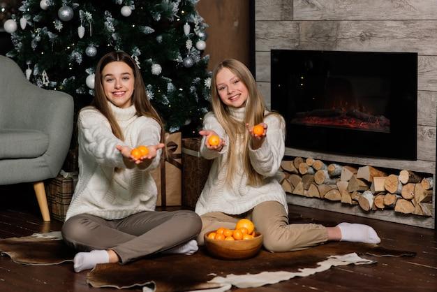Fidanzate che festeggiano il capodanno e il natale e mangiano mandarini sul letto. ci sono regali e rami di abete decorati con palline d'oro.