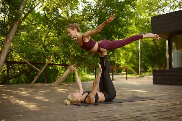 Fidanzate che fanno esercizio di equilibrio sulla formazione yoga di gruppo nel parco estivo. meditazione, lezione in forma sull'allenamento all'aperto