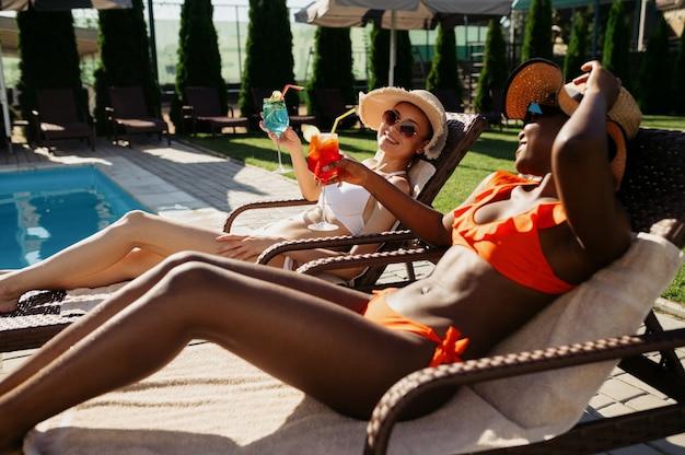 Le amiche bevono cocktail sui lettini in piscina