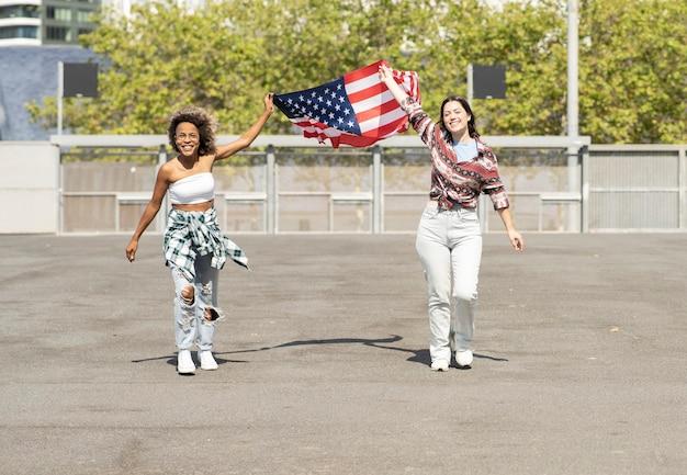 Le amiche tengono felicemente una bandiera degli stati uniti mentre camminano