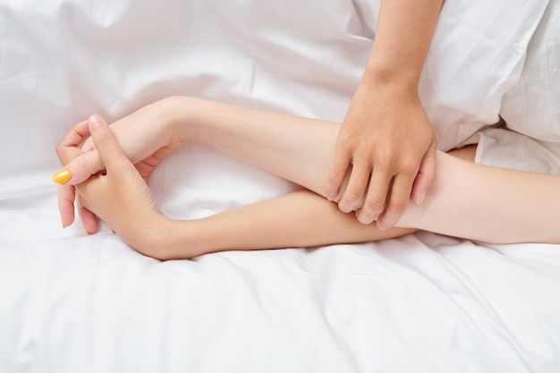 Fidanzate che tengono le mani sul piumone bianco sul letto, vista dall'alto
