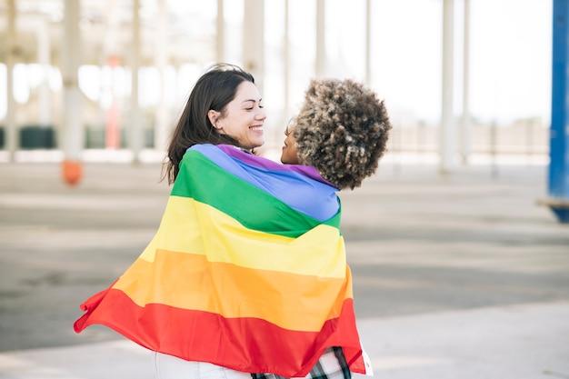 Le amiche si abbracciano mentre sono coperte da una bandiera lgtb