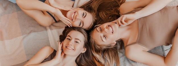 Le amiche ridono a casa sdraiato sul pavimento sui cuscini