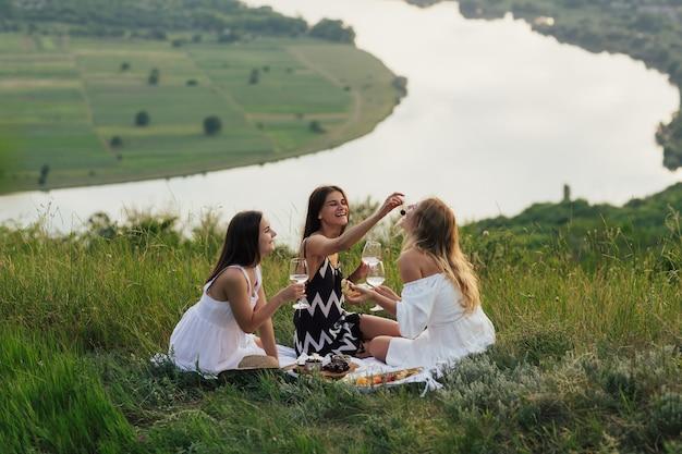 Fidanzate che si siedono sul plaid sull'erba verde con i bicchieri di vino bianco