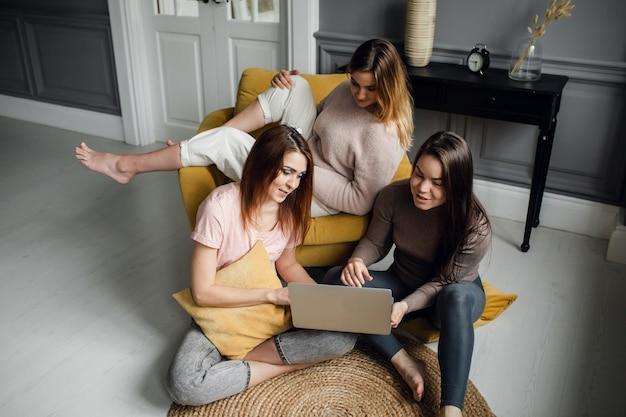 Gli studenti delle amiche svolgono compiti insieme su un laptop a casa