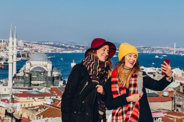 Le amiche fanno un selfie sul tetto del grand bazaar, istanbul, turchia. due ragazze sorridenti sono fotografate al telefono sullo sfondo di istanbul in una limpida giornata invernale.