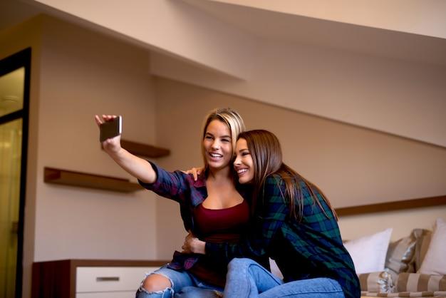 Fidanzate che prendono selfie rilassandosi a casa e si divertono