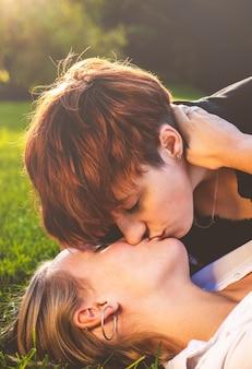 Le ragazze si accoppiano nell'amore baciare sdraiati sull'erba in un parco in una giornata di sole