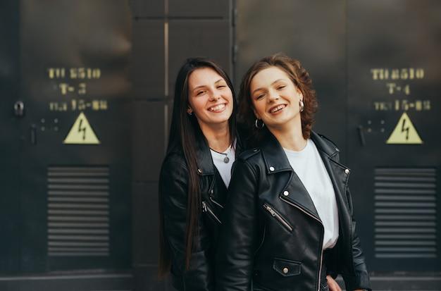 Ragazze in giacche di pelle scura in piedi contro un muro nero