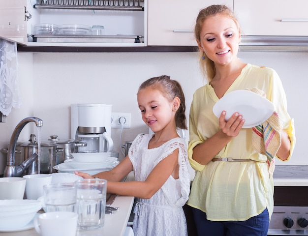 Ragazze che fanno e puliscono i piatti in cucina