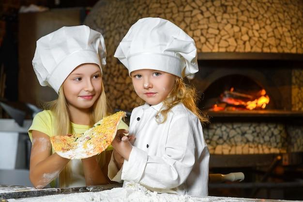 Ragazze vestite da cuoco che prepara la pizza