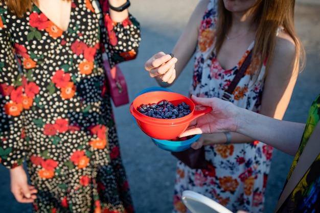 Le ragazze mangiano bacche di caprifoglio blu o lonicera caerulia