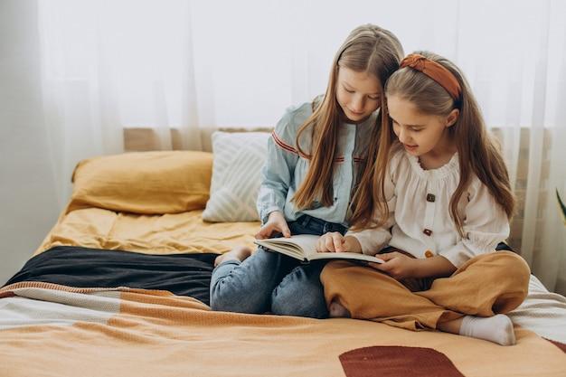 Amici di ragazze che leggono il libro insieme a casa