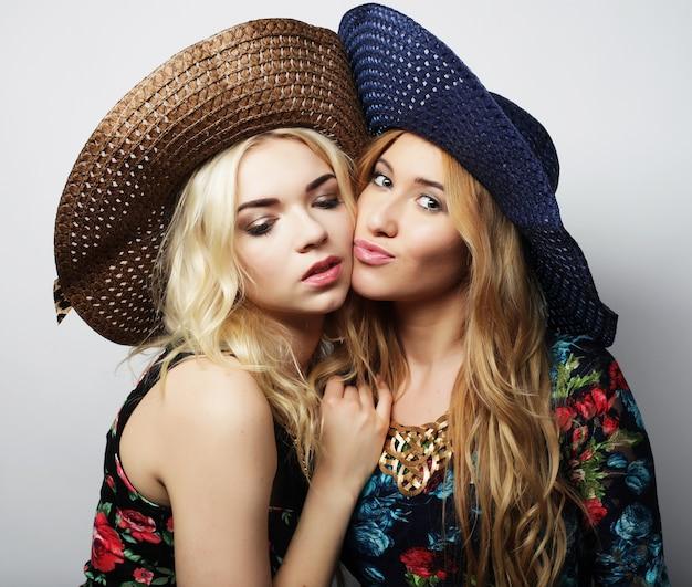 Amici di ragazze che indossano abiti estivi e cappelli di paglia che ridono e si abbracciano